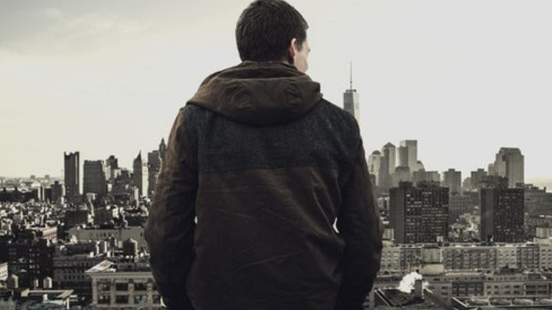 Man looking over city, thinking about the urban survival skills he needs to learn.