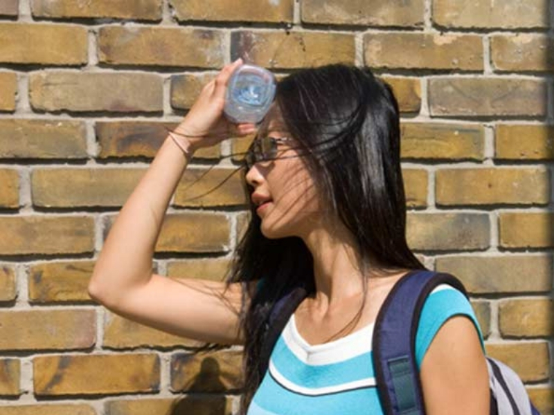 Girl cooling her head off with a bottle of cold water