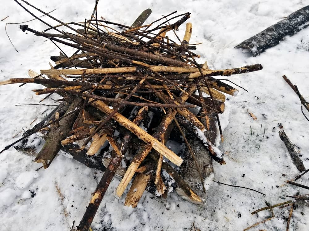 The Pyramid or Upside Down Campfire is an excellent option if you can't find dry fuel. The fire on top will dry out the damp wood below until it is dry enough to catch.